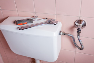 toilet with tools on top