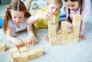 three children playing with wooden blocks