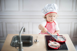 A toddler pretending to cook in his play kitchen.