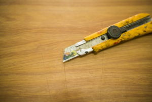 Stained, yellow utility knife laying on a piece of wood.