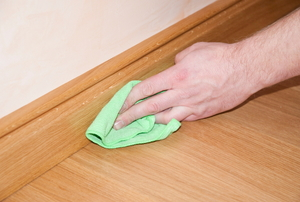 A hand wiping a baseboard with a green cloth.