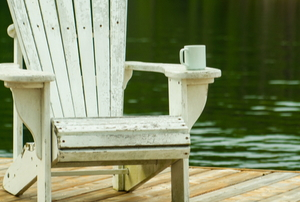 wooden Adirondack chair on a platform by water with a mug