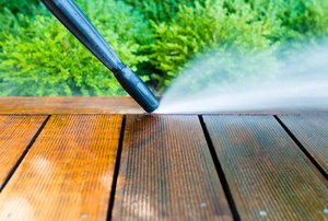 pressure washer cleaning dirt off a wooden patio