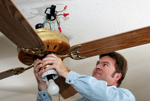 man working on a ceiling fan fixture