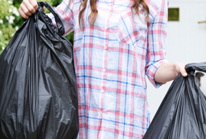 woman carrying two bags of garbage