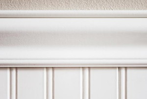 beadboard wainscoting with trim under a stucco wall