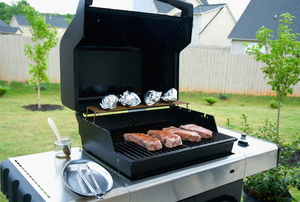 grilling meat on a natural-gas barbecue in the backyard
