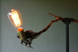 A DIY lamp made of plumbing parts, baling wire and oak branches.