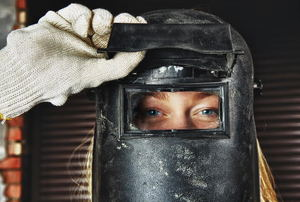 A female welder lifting up the guard on her welding mask.