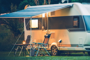 RV with chairs set beneath an awning