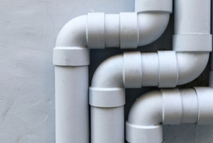 three sets of white PVC pipes against a gray wall