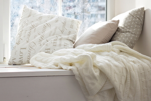 comfy pillows and blanket by a chilly window in winter