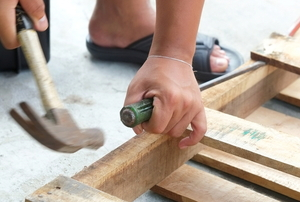 hands using hammer and chisel to break down wood pallet