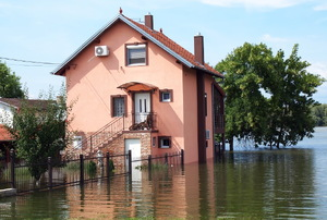 A pink house surrounded by floodwaters.