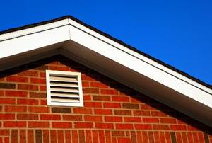A white gable vent on a brick house.