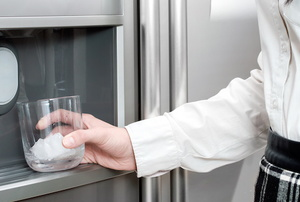 woman getting ice from ice maker in refrigerator
