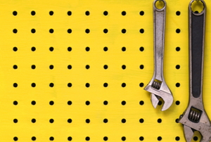 yellow painted pegboard with hanging wrenches