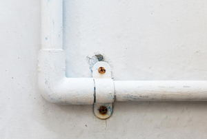 A pipe line on the side of a house.