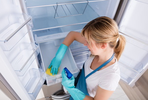 A woman cleaning a fridge.
