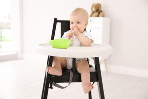A baby in a wooden high chair.