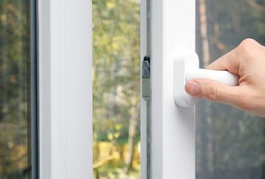 Person shutting a white storm door