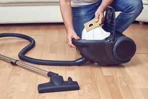 A woman empties a vacuum.