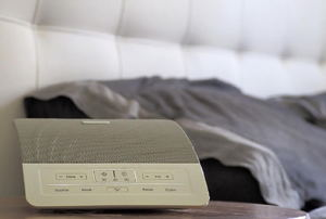 alarm clock with bed in the background