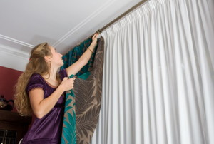 woman hanging drapes