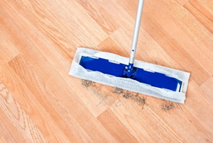 Swiffer sweeping up dirt and debris off of a wood floor.