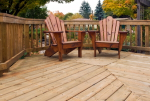 Two wooden Adirondack chairs on a backyard deck.