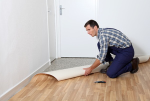 Linoleum flooring being rolled out by a person