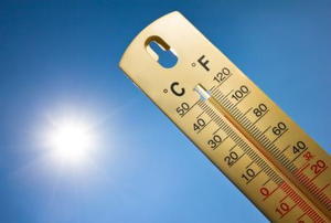A thermometer with the sun in the background.