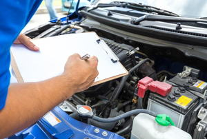 A man holding a checklist looking at a car engine.
