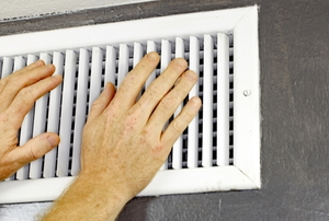 hands checking drafts from heating vents
