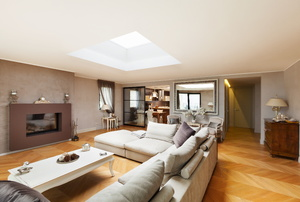 living room with large couch, fireplace, coffee table, and skylight