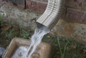 A downspout gushing rainwater onto a splash block.