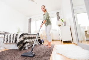 A woman vacuums a bedroom.
