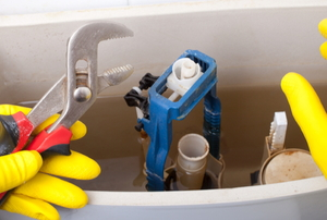 gloved hands fixing open toilet tank with plumbing wrench