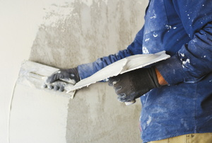 A man applying white putty to a wall.