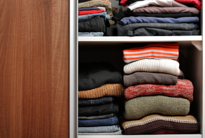 closet sliding door open, exposing folded clothes