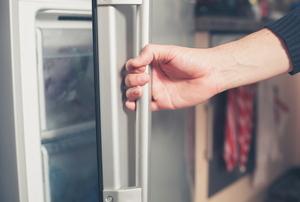 A hand opening a refrigerator door.