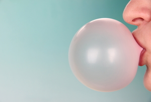 A person blowing a bubble in chewing gum against a blue background.