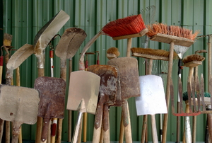 A grouping of outdoor tools against a green shed.