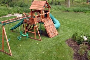 A cedar swing set in a backyard.