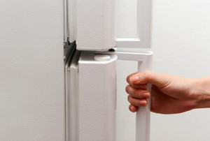 A hand on the handle of a white refrigerator.