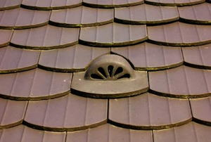 A matching roof vent in the midst of brown shingles.