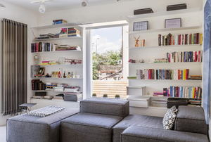 A living room with bookcases around a window.