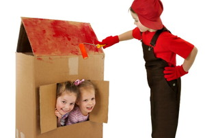 children playing with a cardboard house