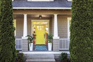 Front porch with railing, yellow door, rug, and potted plants