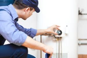 A repair man fixing a hot water heater.